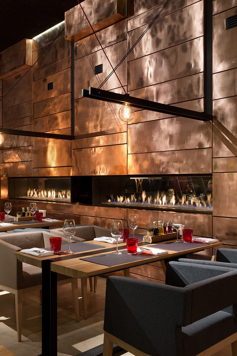 A wall made of copper panels add shine and texture to the interior of this restaurant.