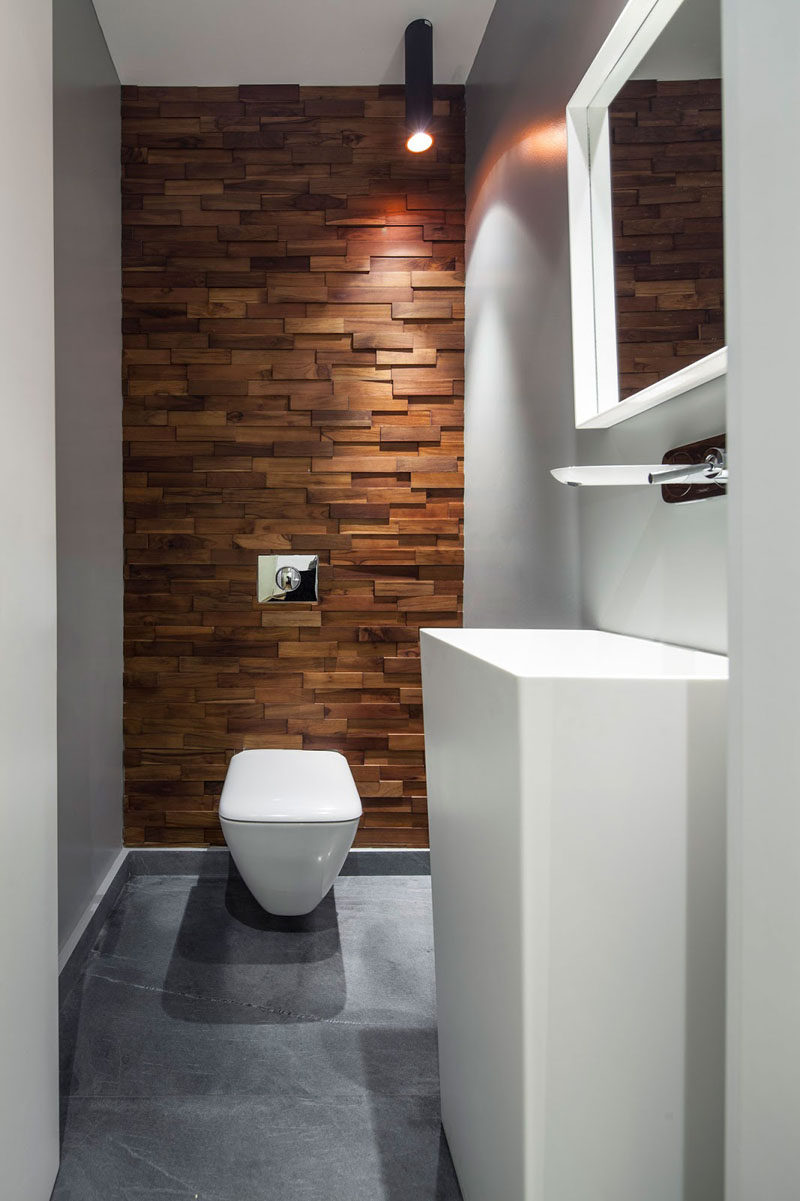 Accent Wall Ideas - 12 Different Ways To Cover Your Walls In Wood // Thin wood blocks running up this wall soften the industrial feel created by the concrete floor and warm up the white bathroom elements.  #AccentWall #FeatureWall #WoodAccentWall #WoodFeatureWall #InteriorDesign