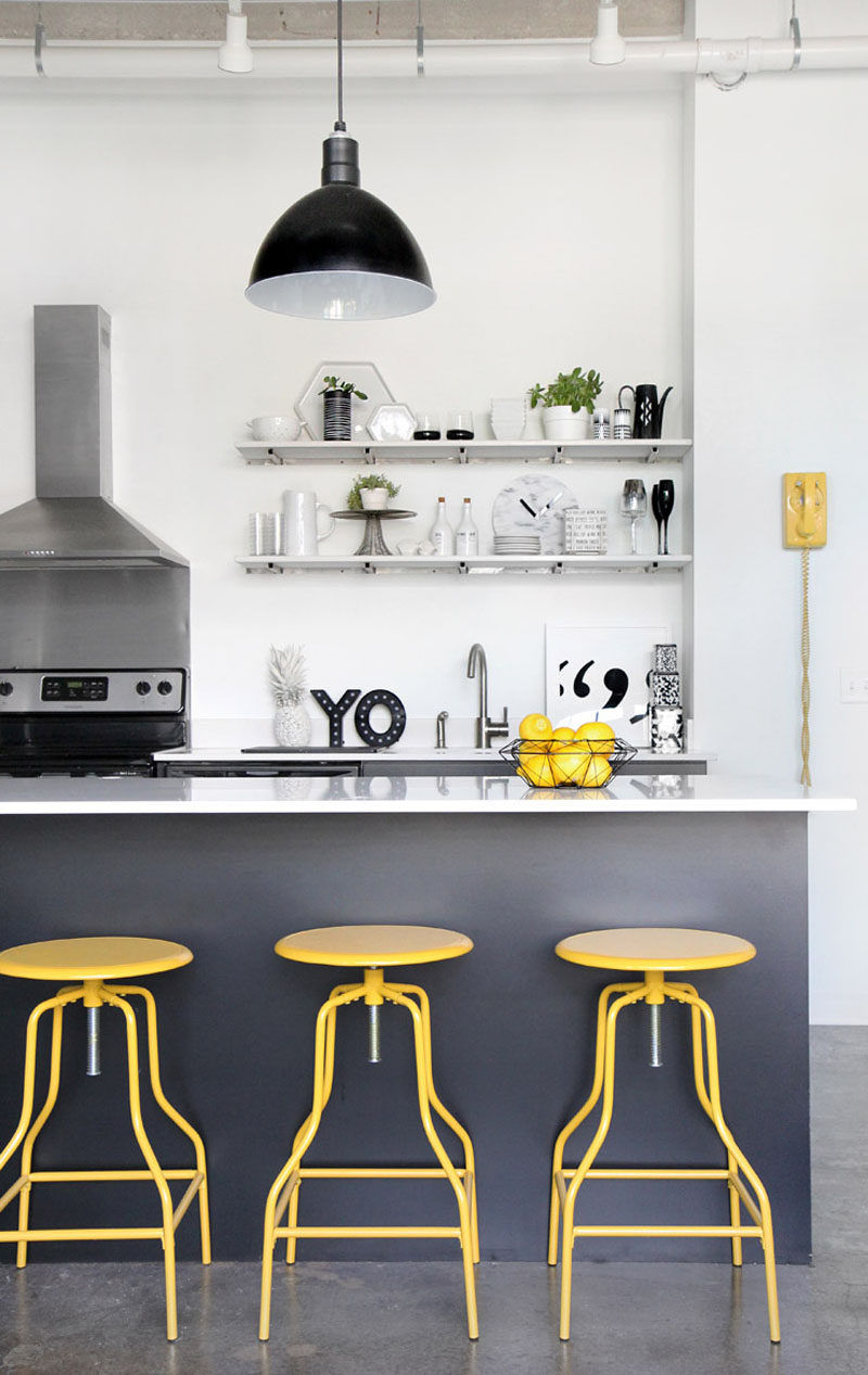 Palette Profile - Yellow, Gray and White Interiors // This mainly white and gray kitchen is infused with life thanks to the yellow bar stools, bowl of lemons, and vintage-style phone on the wall.