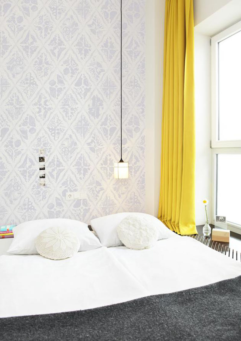 Palette Profile - Yellow, Gray and White Interiors // Yellow curtains have been combined with soft gray patterned wallpaper and a white bedspread with dark gray throw blanket, to make this hotel room calm and relaxing.