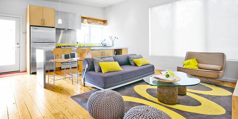Palette Profile - Yellow, Gray and White Interiors // Small yellow details, like the throw pillows, design in the rug, and the kitchen backsplash, bring in a bit of fun to this bright living space dominated by white walls and gray/silver tones.