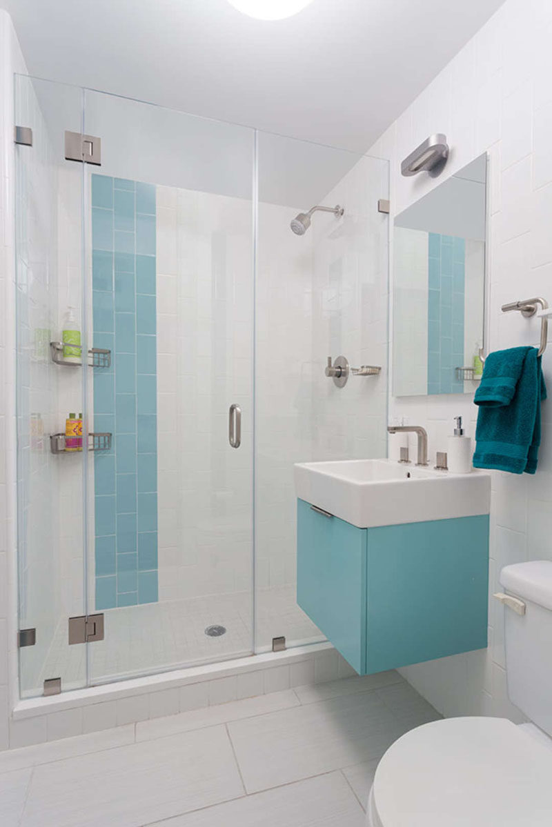13 Inspirational Examples Of Blue And White Bathrooms // A strip of blue in the shower and a blue cabinet add a fun touch of color and break up the all white space.