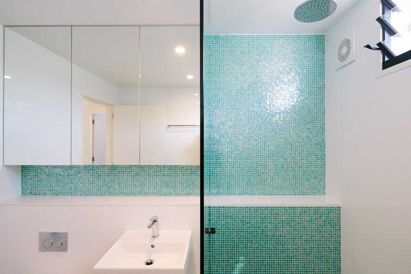 13 Inspirational Examples Of Blue And White Bathrooms // Light aqua tiles line the wall of the shower and the backsplash of this bathroom helping to create a unified, relaxing space.