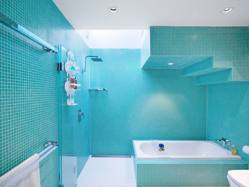 13 Inspirational Examples Of Blue And White Bathrooms // Blue tiles covering the walls and tub of this bathroom make it bright and playful, while the white bath, shower floor, toilet and caddy help make the space feel clean and fresh.
