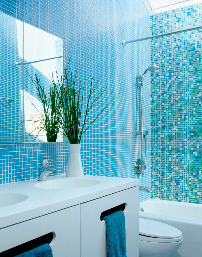 13 Inspirational Examples Of Blue And White Bathrooms // Blue tiled walls broken up by an accent wall of different shades of blue tiles, coupled with the white vanity, make this bathroom fun yet calm.