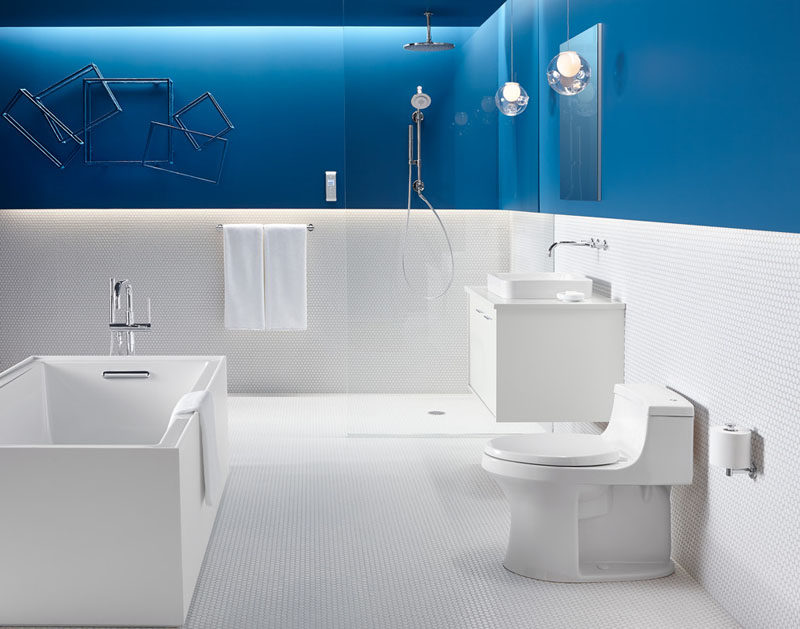 13 Inspirational Examples Of Blue And White Bathrooms // This all white bathroom is interrupted by a bold strip of blue that continues all the way to the ceiling.