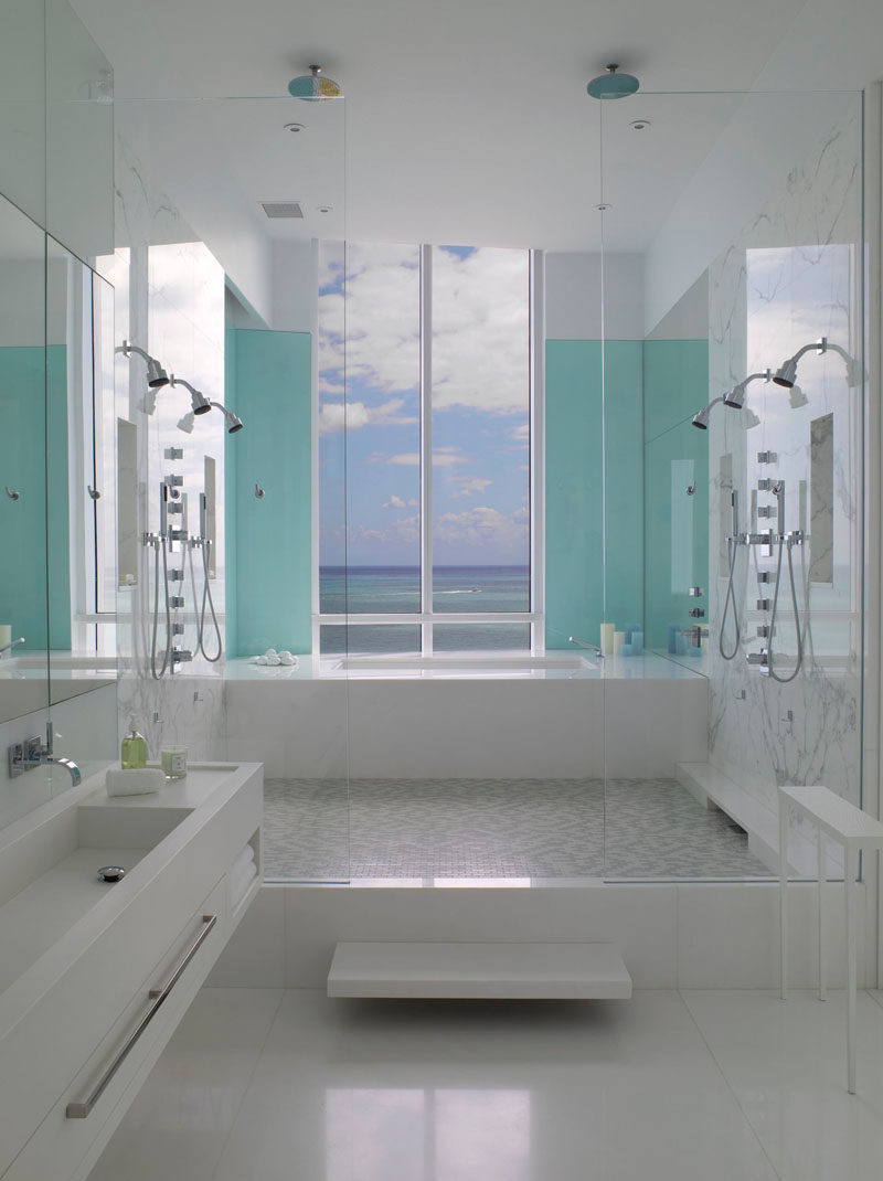 13 Inspirational Examples Of Blue And White Bathrooms // Two light blue panels flank the window of this bathroom, drawing your eye to the window and framing the incredible view just outside.