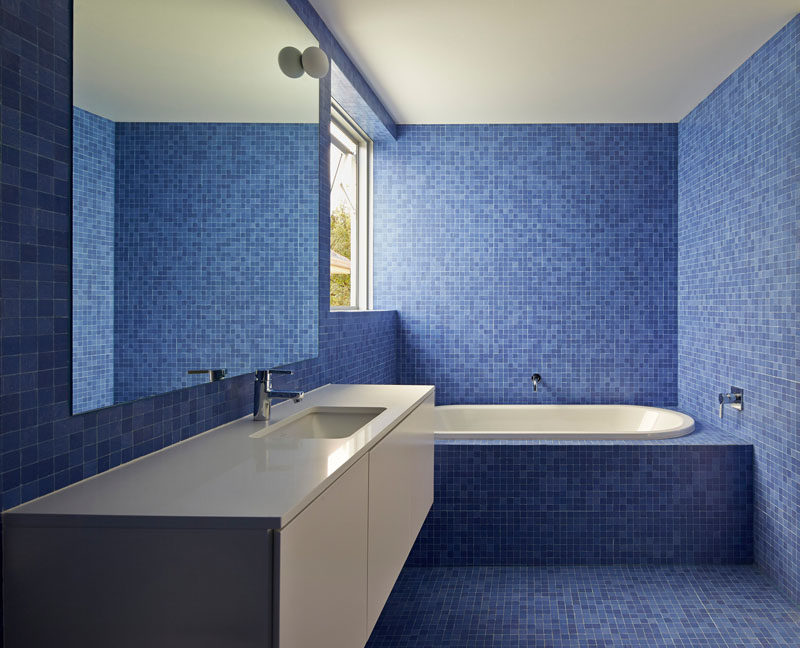 13 Inspirational Examples Of Blue And White Bathrooms // Various shades of blue tiles line the walls and floor of this bathroom, creating a fun atmosphere with a touch of sophistication thanks to the white tub and counter.