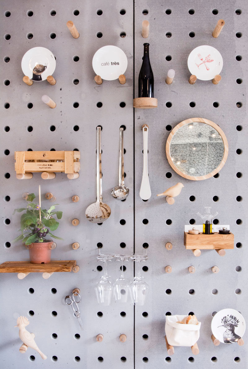 Wall Decor Idea - A gray perforated concrete pegboard lines the wall of this cafe for a unique shelving solution