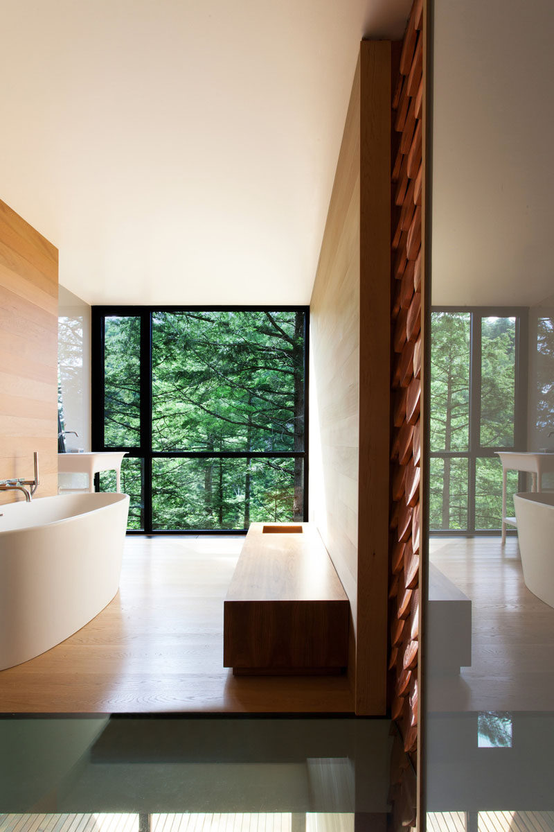 This bathroom has a large floor-to-ceiling window that provides views of the forest outside.