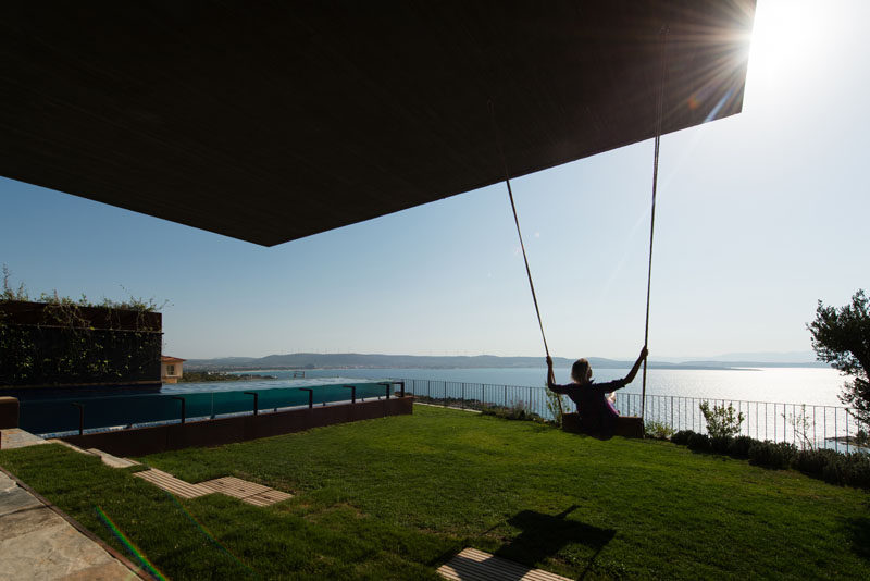 This grassy backyard has a swing and a swimming pool, both positioned to take advantage of the water views.