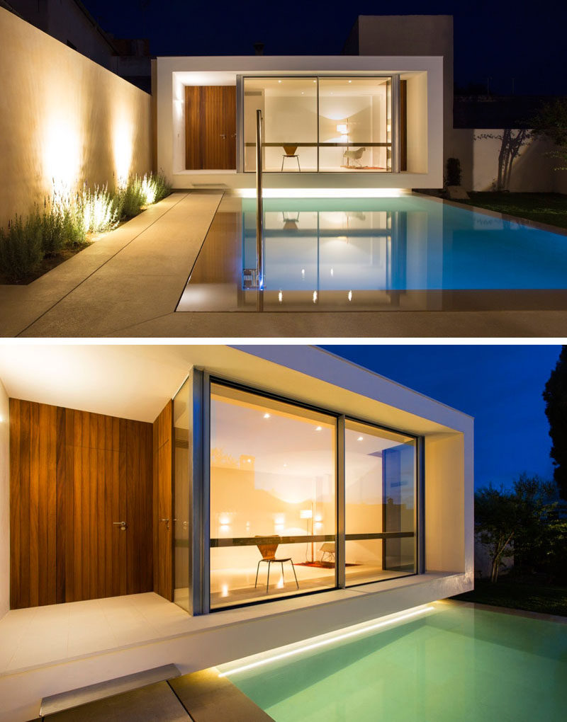 A small pool is positioned between a house and studio space, with lighting highlighting the dramatic design of the garden and patio.