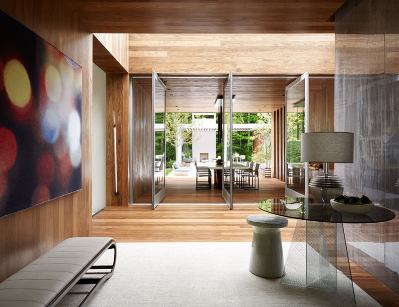 Large glass doors pivot to open the interior of the home to the covered outdoor dining area and backyard.