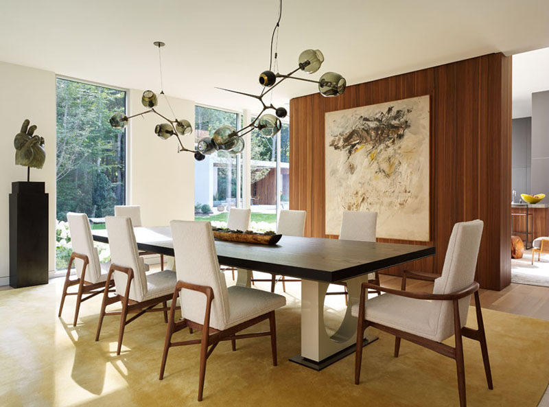 A sculptural light fixture anchors this dining table in the space, and a partial wall separates it from the living room.