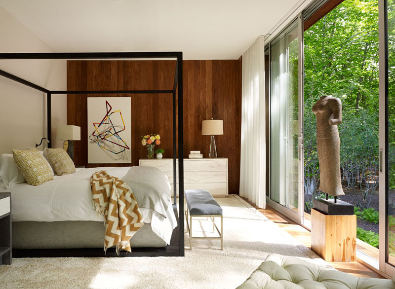 This bedroom has a wooden feature wall and sliding glass doors provide access to the landscaped backyard.