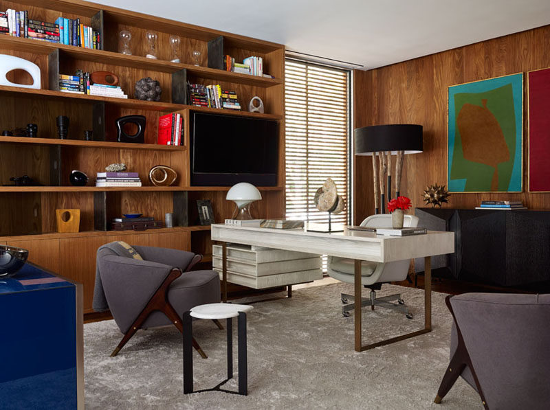 This home office has built-in wooden shelving and enough room for multiple furniture pieces.