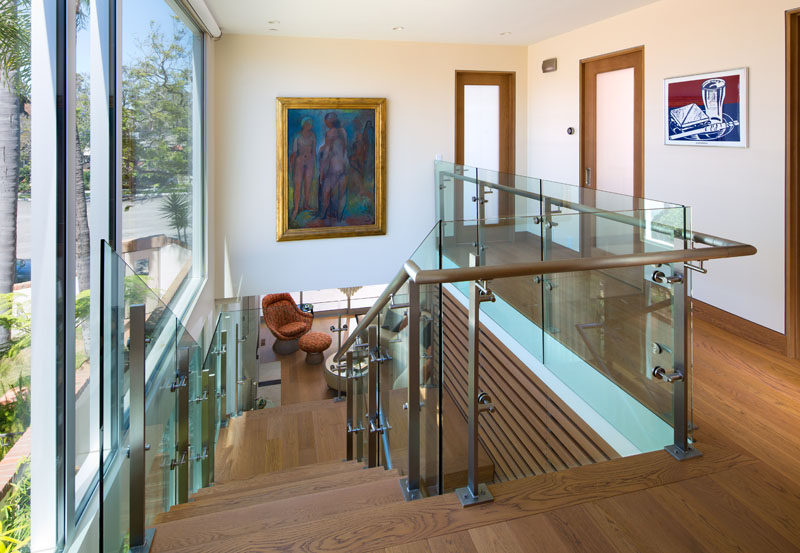 These wood stairs have wooden handrails and glass safety barriers.