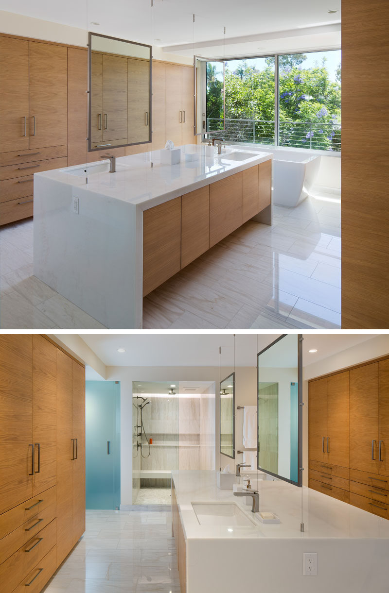 In this ensuite bathroom, there's a large central island vanity, that has a basin and mirror on each side.