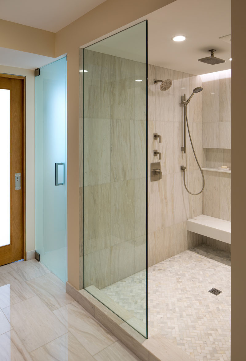 In this shower, there are multiple shower heads to choose from, as well as a built-in bench and shelf.