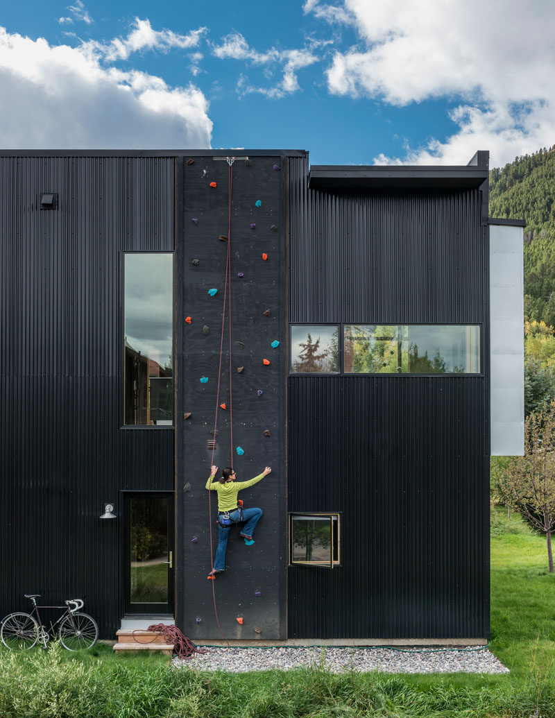 The exterior of the home is clad in black corrugated metal and was chosen for its durability, texture and low cost. Due to the height of the home, the designers were also able to install a climbing wall.