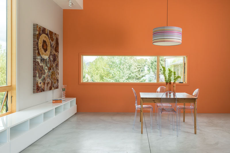 This dining area has a bright orange feature wall to draw your eye to the horizontal window.