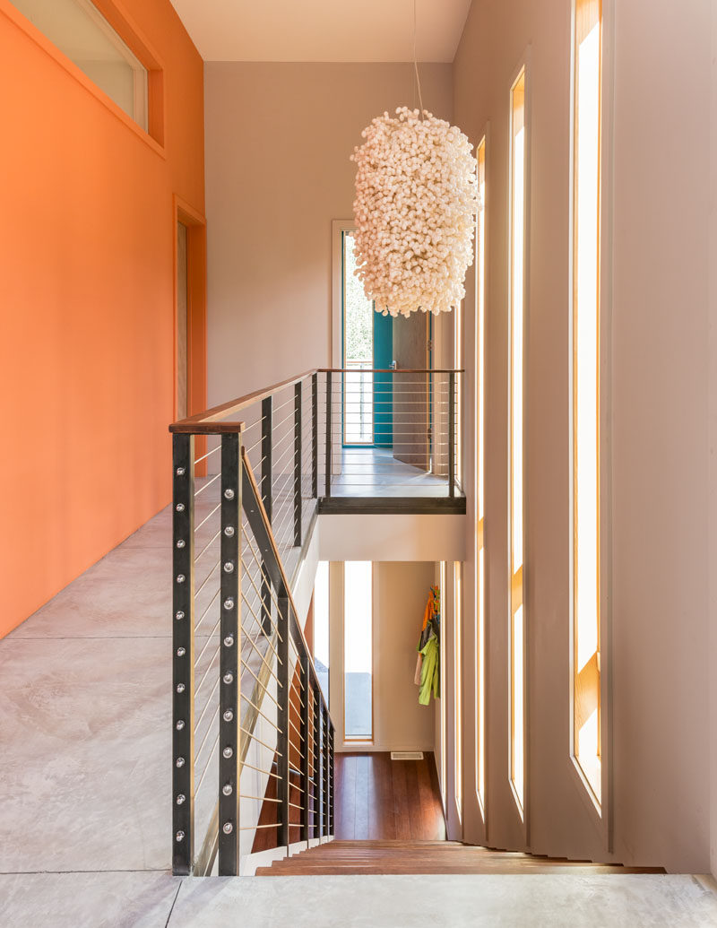 Long windows provide plenty of natural light to this staircase, and the brightly colored walls draw your eye upstairs.