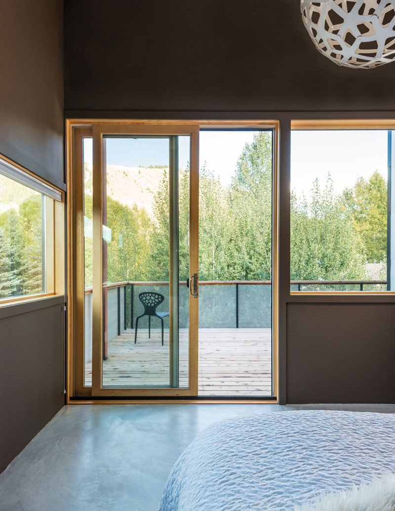 In this bedroom, windows and a private balcony provide views of the surrounding mountains.
