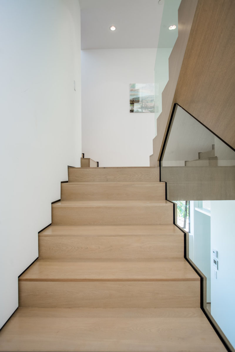 Light wood stairs have been paired with white walls and glass for a contemporary look in this home.