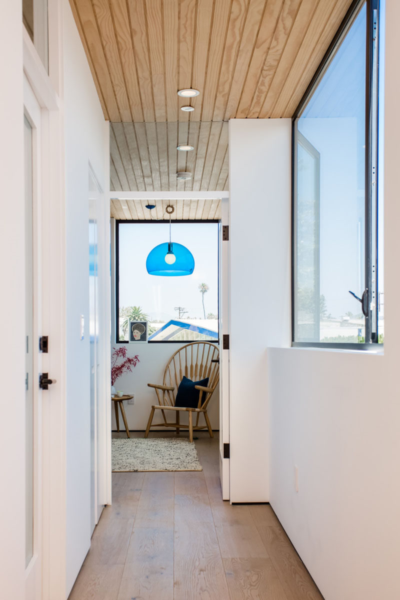 A bright blue pendant light guides to the bedroom in this all-white and wooden hallway.