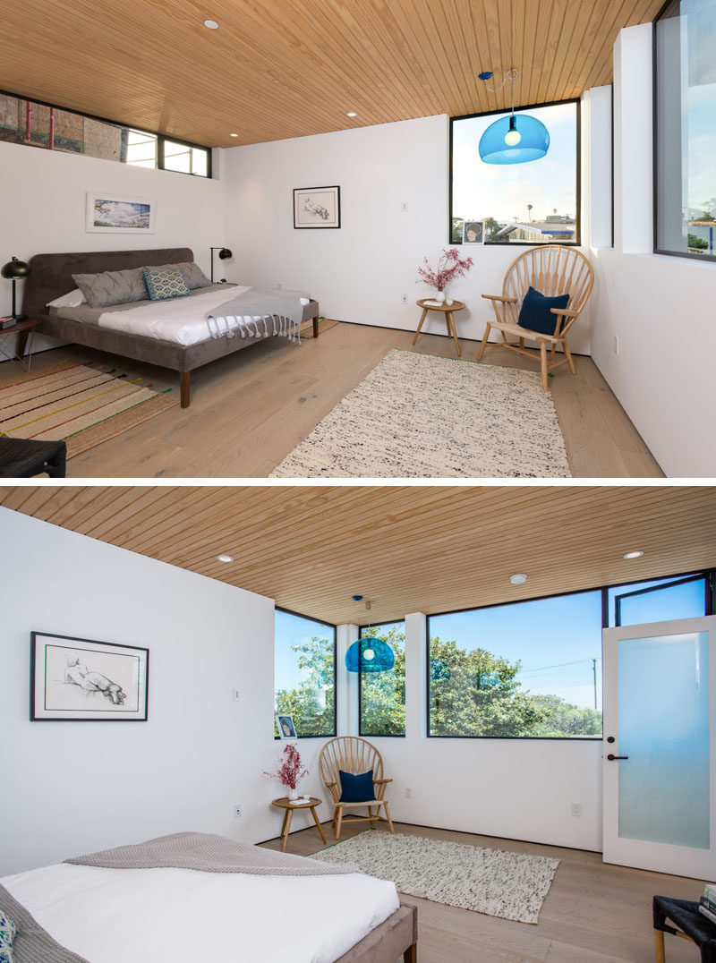 This bedroom has windows of various sizes allowing for plenty of natural light. White walls have been paired with a wooden ceiling and floor for a contemporary bedroom look.