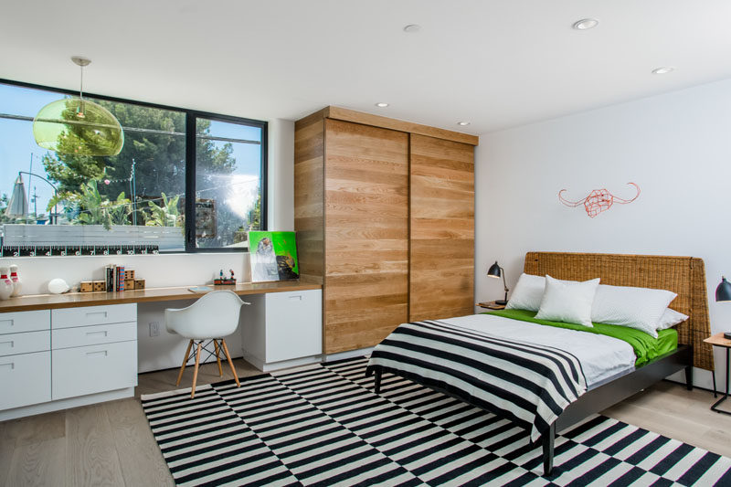 In this teen bedroom, a built-in desk has plenty of storage and a wooden closet provides space for lots of clothes. A black and white striped rug and blanket are fun, lively additions to the room.