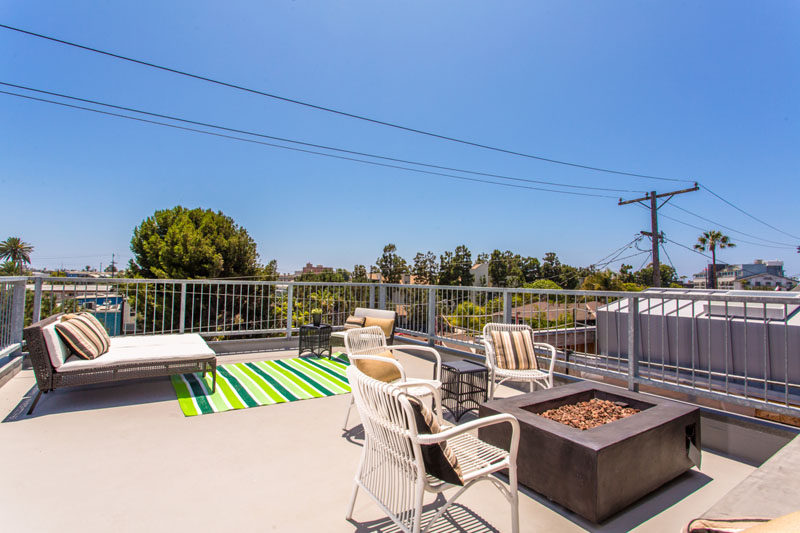 The rooftop of this home has two different seating areas, one for lounging in the sunshine, and the other for gathering around the standalone fireplace.