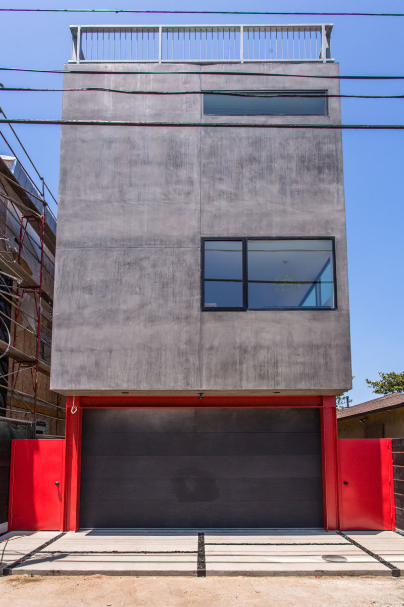 At the rear of this Californian house, you can easily tell where the garage is as it's highlighted with a bright red surround. The black garage door matches the black window frames of the home.