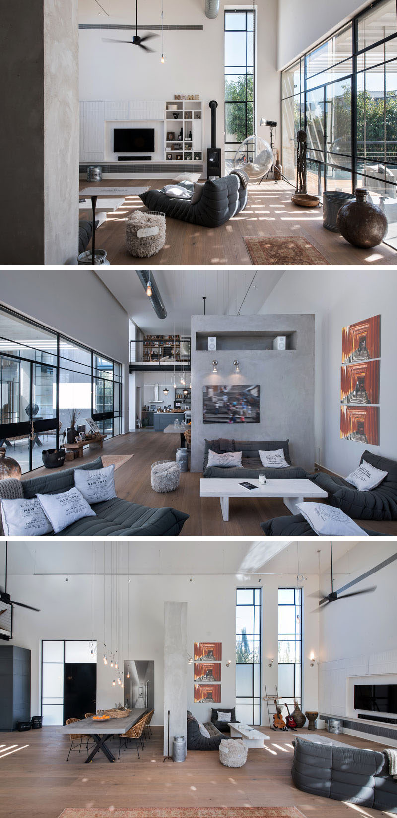 This home has a double-height ceiling accompanied by large windows with black frames. In the living area, comfortable couches are focused on the television, and a partial wall divides the open space to define the dining area.