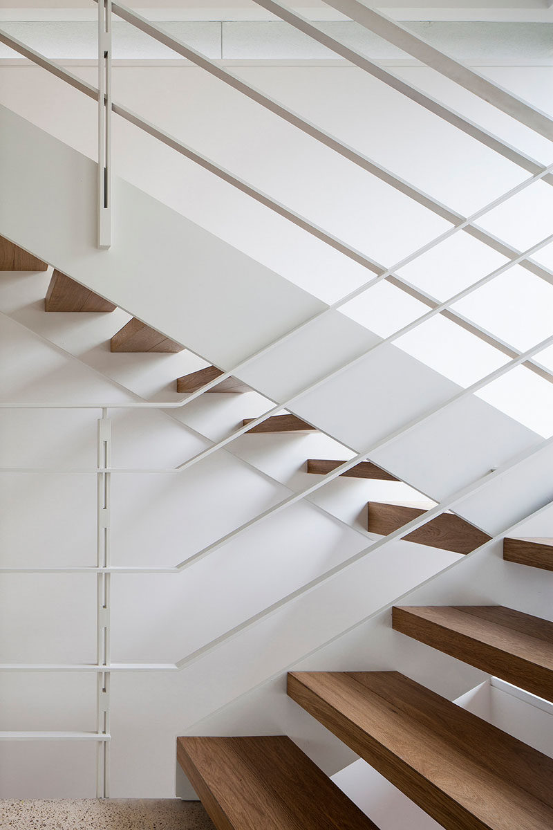 These stairs have wooden treads and metal handrails painted white.