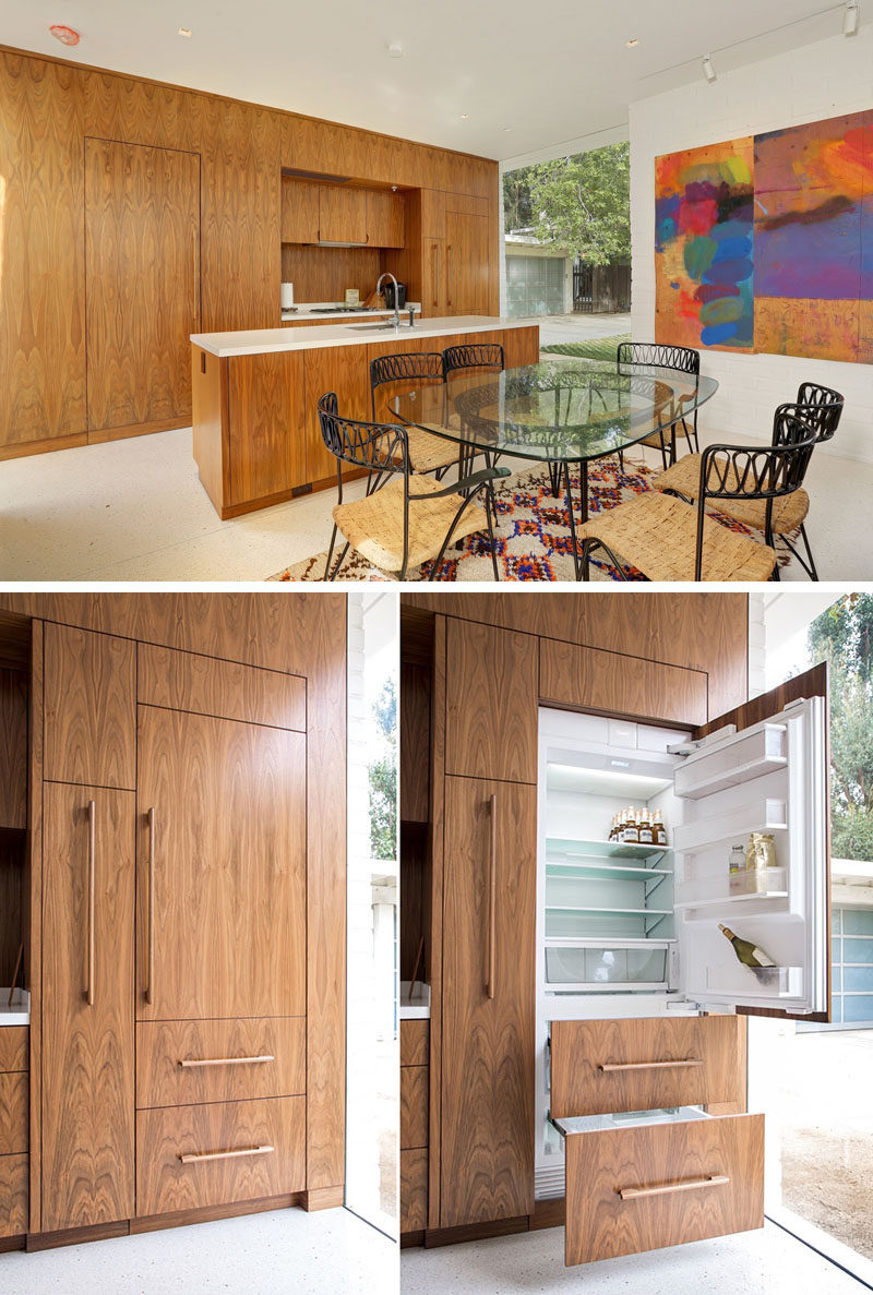 This kitchen has a long island with a lightly colored countertop that contrasts with the wood cabinetry. The hidden door on the left is a small powder room, and the door panel on the right is the integrated fridge.