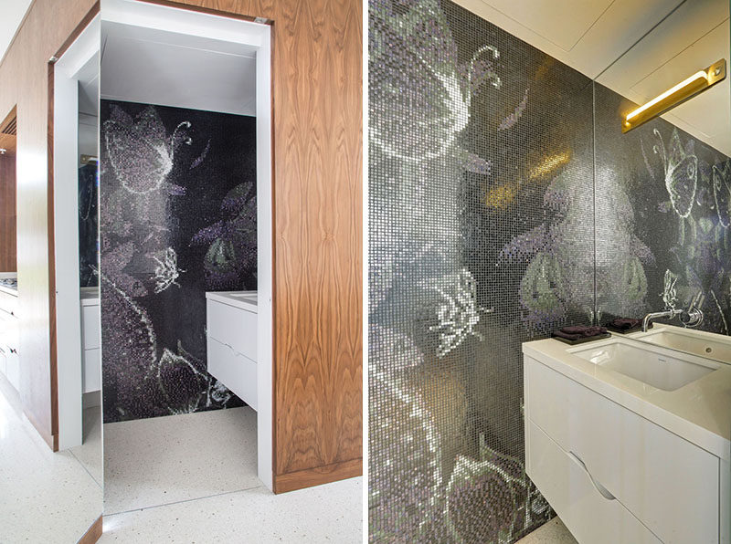 In this hidden bathroom there's a tile mural that covers the wall and adds an artistic element to the space.