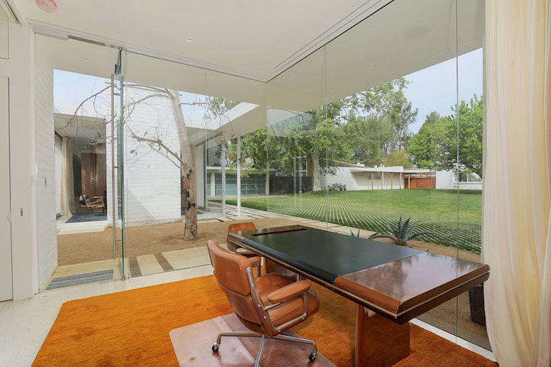 This home office with floor-to-ceiling glass windows looks out to the main house and the backyard.