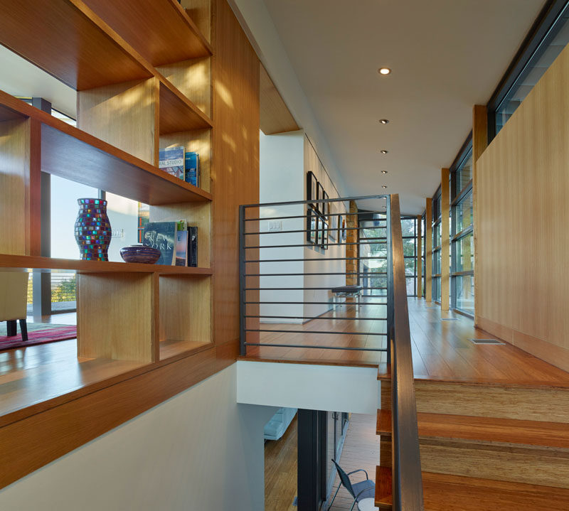 Custom shelving provides a separation between the front gallery-like entrance to the home, the stairs and the living room.