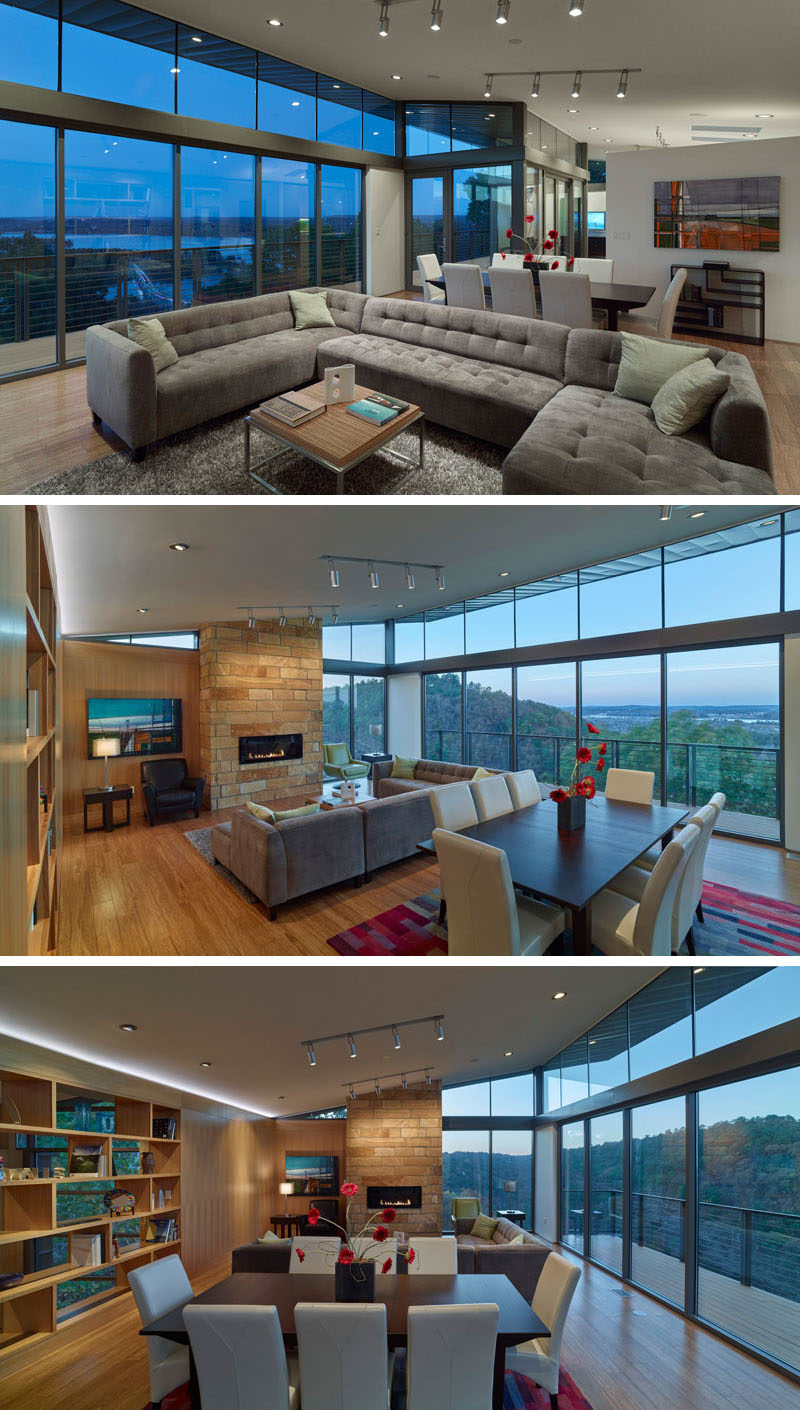 A wall of glass with access to the balcony allows for a picturesque view from the living and dining area of this home, as well as the kitchen. In the living room, the couch is focused on the stone fireplace hearth. Sharing the space is also the dining room, positioned between the living room and the kitchen.