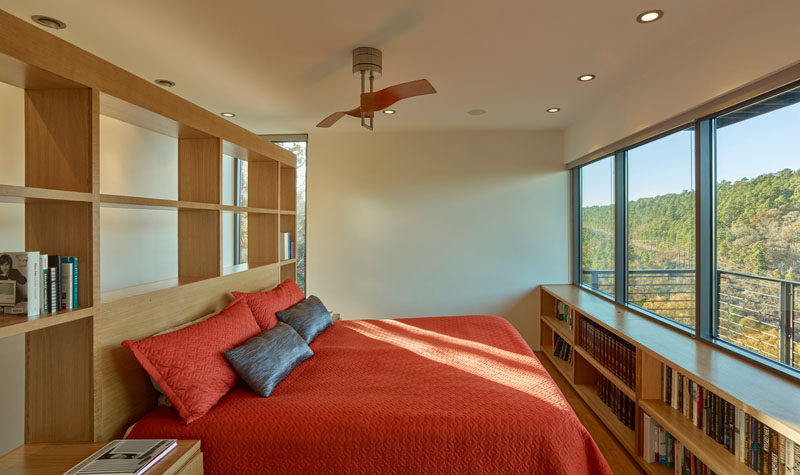 This master bedroom has custom woodworking with plenty of shelving, and the bed positioned to take advantage of the views.