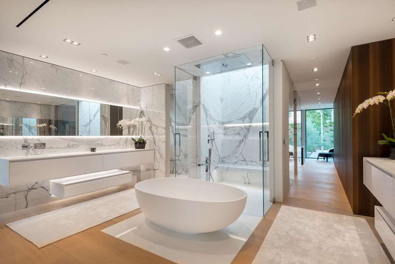 In this master bathroom the designers have used Nano Glass, a scratch & stainproof stone composite slab. The bathroom also has a shower with two doors, a standalone bathtub and a large vanity with backlit mirror.