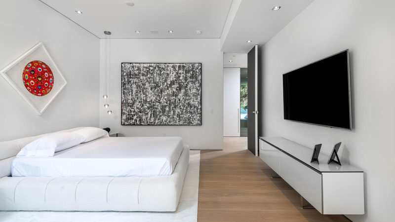 A simple black, white and wood color palette has been used in this bedroom, with a pop of red adding a touch of fun to the room.