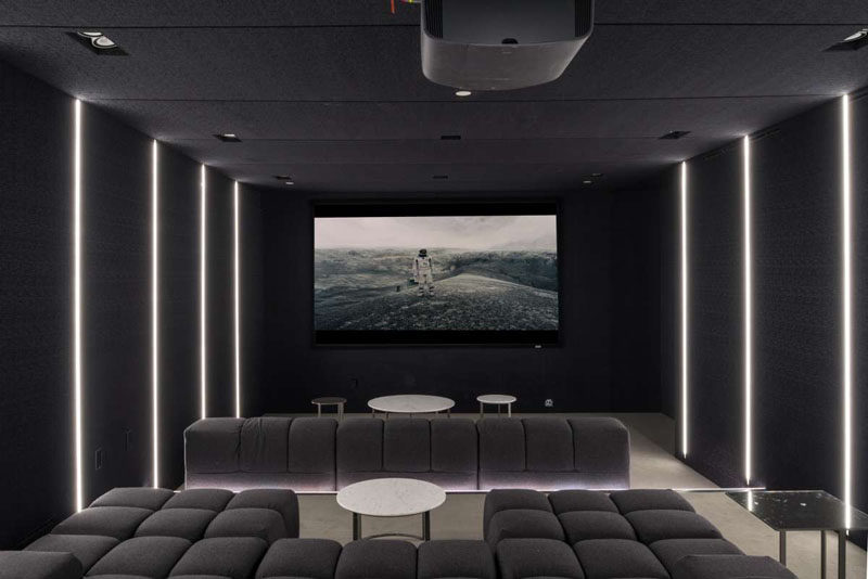 This contemporary home has a dark home theatre room, with comfortable couches and black walls.