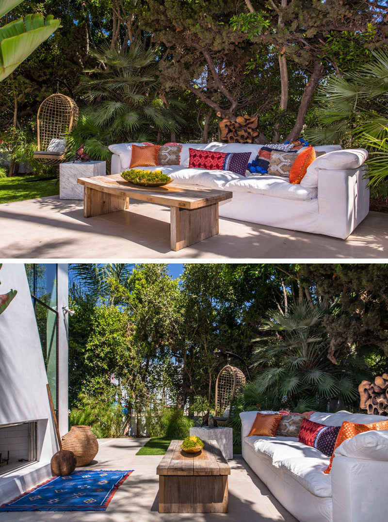 This outdoor space has been set up with a large white sofa and a wooden coffee table. Colorful accents have been added in the form of a blue rug and a few bright throw pillows.
