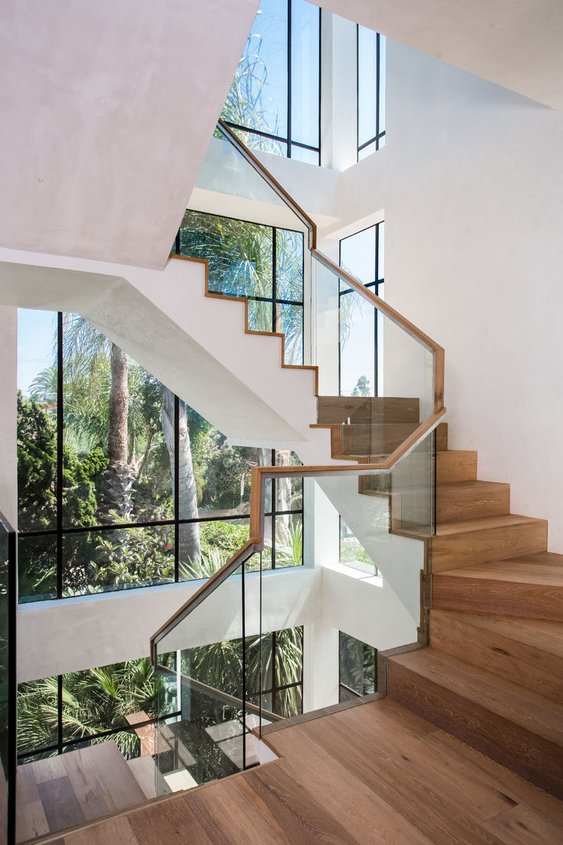 Windows surround these wooden stairs leading you to the upper level of the home.