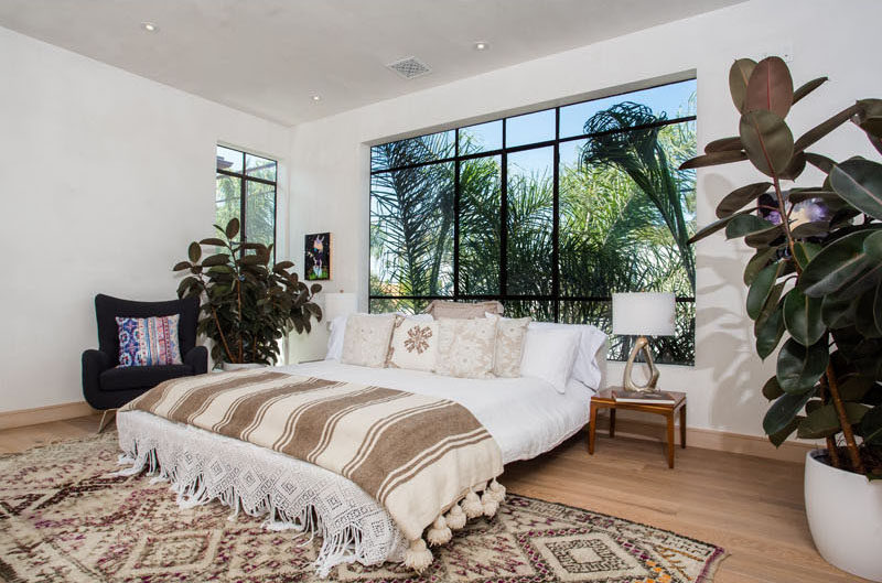 Lots of light enters this bedroom through the large black-framed windows.