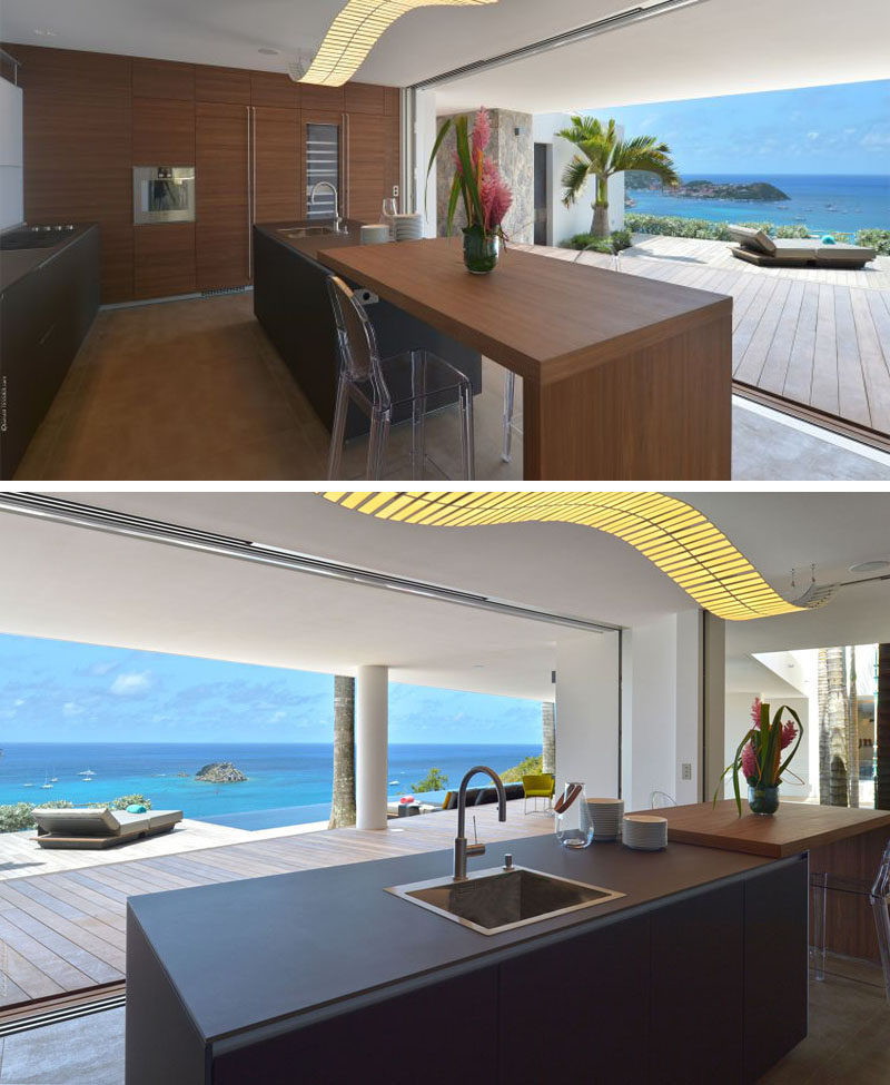 The glass wall in this kitchen can be opened to let in the warm breezes coming off the ocean and makes dinner prep so much more enjoyable. A large island incorporates seating for quick snacks.