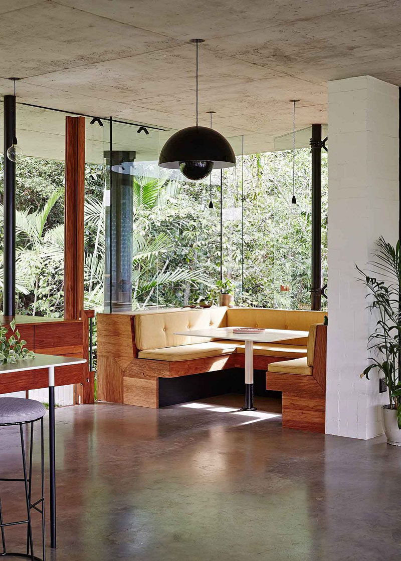 Dining Room Idea - Create A Built-In Dining Nook // Windows surrounding this built in dining area ensure that everyone at the table has incredible views of the rainforest outside. Upholstered cushions have been designed to match the dimensions of the benches. #DiningNook #BuiltInDiningNook #BanquetteSeating #DiningRoom