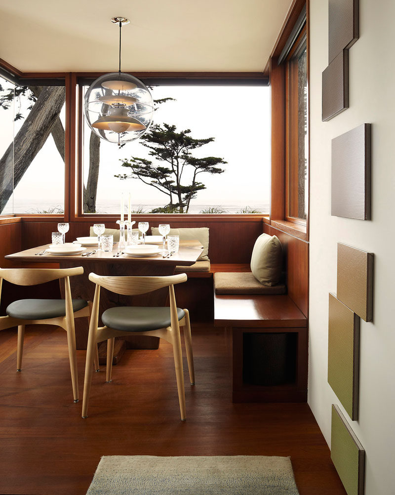 Dining Room Idea - Create A Built-In Dining Nook // The dark wood of the built-in seats is offset by the huge windows looking out over the ocean that brighten up the whole space. #DiningNook #BuiltInDiningNook #BanquetteSeating #DiningRoom